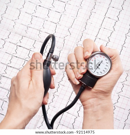 blood pressure gauge in the hands,ecg as background - stock photo