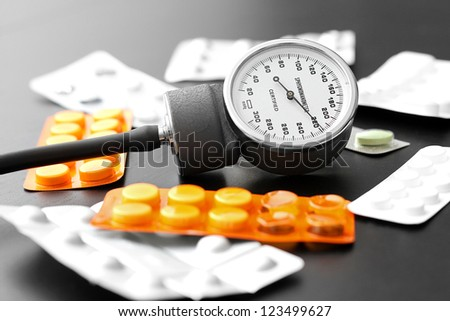 blood pressure instrument and pills on the table - stock photo