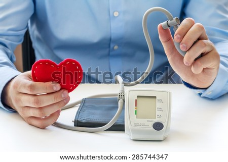 Blood pressure measuring concept. Doctor sitting at the white table and take digital blood pressure monitor and red soft heart in the hands - stock photo