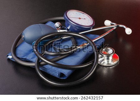 Blood pressure measuring device on isolated black background - stock photo