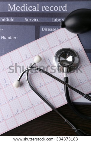 Blood pressure meter and stethoscope, on dark wooden background - stock photo