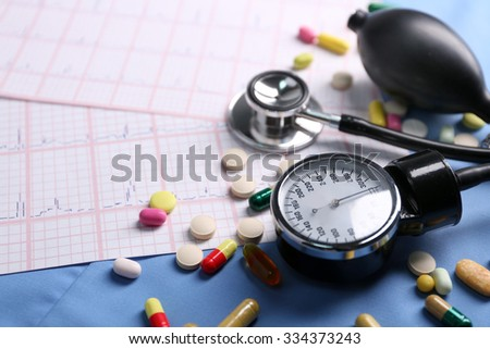 Blood pressure meter, pills and stethoscope, on blue uniform background - stock photo