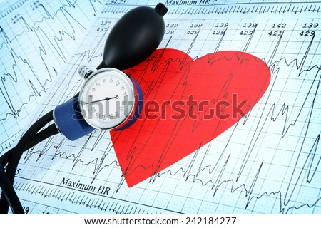Blood pressure monitor on heart printout with heart shape - stock photo