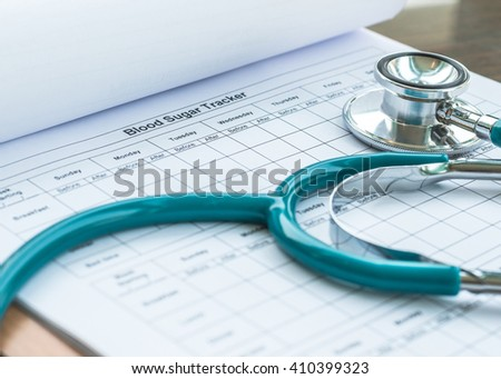 Blood sugar tracker record blank paper form for patients with diabetic illness in clip pad on doctor/ physician/ therapist's working table desk with stethoscope: World health diabetes day concept  - stock photo