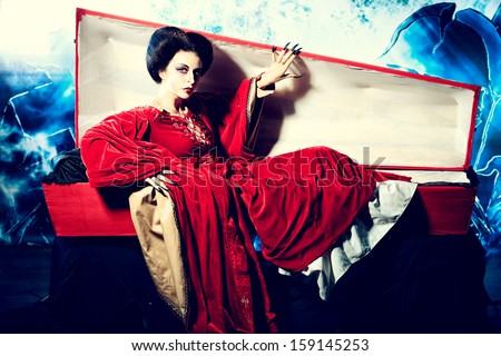 Bloodthirsty female vampire rises from the coffin on the night cemetery. - stock photo
