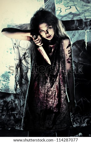 Bloodthirsty zombie with a knife standing at the night cemetery in the mist and moonlight. - stock photo