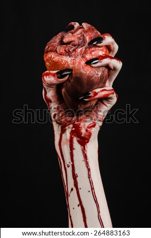Bloody horror and Halloween theme: Terrible bloody hands with black nails holding a bloody human heart on a black background isolated background in studio - stock photo