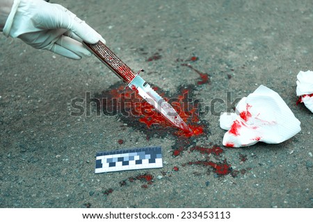 Bloody knife dragged along outdoors - stock photo