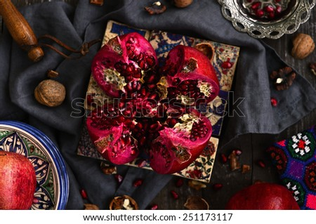 Bloody red ripe pomegranate over traditional pattern Turkish tiles with copy space on wooden background - stock photo