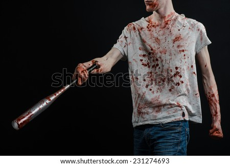 Bloody topic: The guy in a bloody T-shirt holding a bloody bat on a black background - stock photo