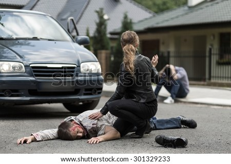 Bloody victim of car accident lying on the street - stock photo