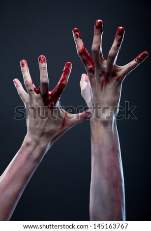 Bloody zombie hands, studio shot over gray background - stock photo