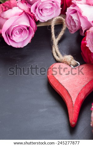 blooming  fresh pink roses  laying  on black  stone  table with heart - stock photo