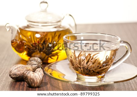 Blooming green tea in glass teacup close up with teapot and  various dry blooming tea on the table - stock photo