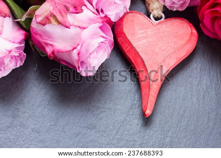 blooming  pink roses  laying  on black  stone  table with heart - stock photo