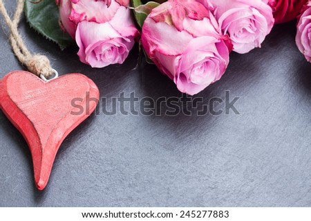 blooming  pink roses  laying  on black  stone  table with heart and copy space - stock photo