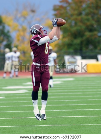 BLOOMSBURG, PA - NOVEMBER 6: Bloomsburg University wide receiver Cory Stiger makes a jumping catch in pregame drills prior to a football game November 6, 2010 in Bloomsburg, PA - stock photo