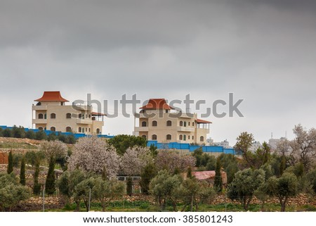 Blossoming almond trees in front of houses on the outskirts of Hebron on the background of a stormy sky - stock photo