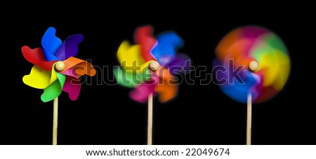 Blowing in the Wind: three toy windmills spinning stationary to fast; isolated on extendable black ground to give good copy-space; high resolution so each image can be used on its own - stock photo