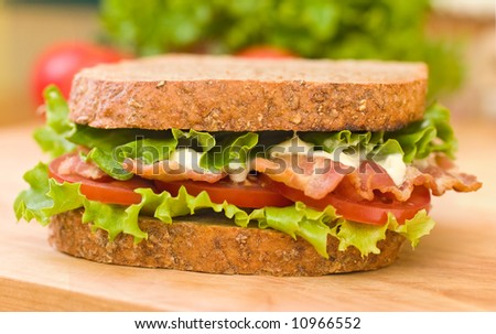 BLT (Bacon, Lettuce, Tomato) sandwich with mayonnaise with fresh vegetables as background - stock photo