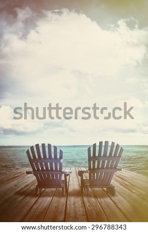 Blue adirondack chairs on dock with vintage textures and feel - stock photo