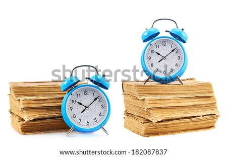 Blue alarm clock next to a books stack isolated over the white background, set of two foreshortenings - stock photo