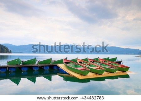 Blue Alps lake with Rental rowing boats in marina. Wharf for trip ships. - stock photo