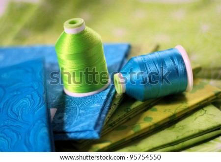Blue and bright green fabric and thread ready for a sewing or quilting project. - stock photo