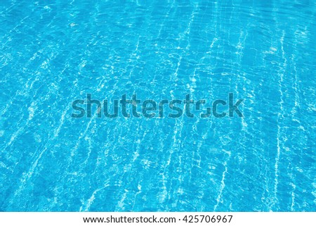 Blue and bright water with sun reflection in swimming pool - stock photo