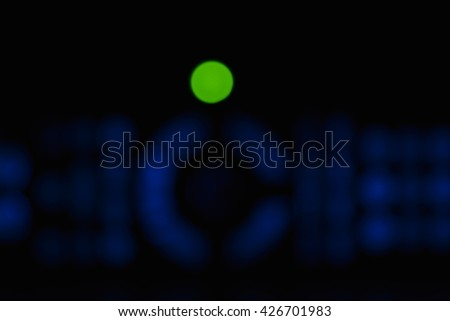 Blue and green defocused blurry soft lights of TV remote glowing softly in the black darkness and placed evently on the photo. - stock photo