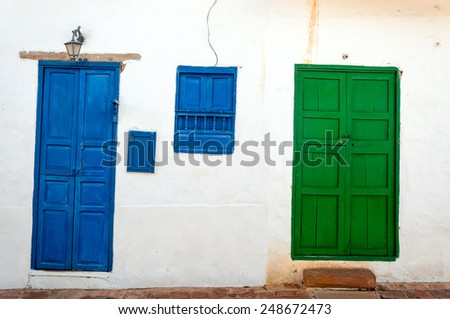 Blue and green doors set against the white facade of a historic colonial building in Barichara, Colombia - stock photo