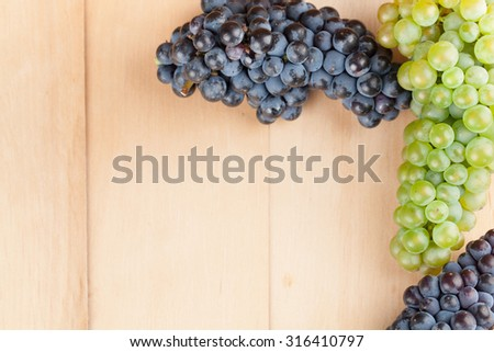 Blue and green grapes frame on wooden background - stock photo