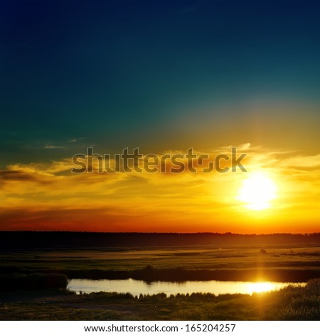 blue and orange sunset over lake - stock photo