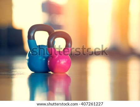 Blue and pink weight with black handles on a a blurred background - stock photo