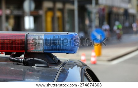 Blue and red flashing sirens of police car during the roadblock - stock photo