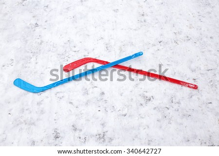 blue and red hockey stick crossed on the ice. kids hockey stick thrown on the ice after the game. it symbolizes the opposing team and their sports fight, passion and desire to win - stock photo