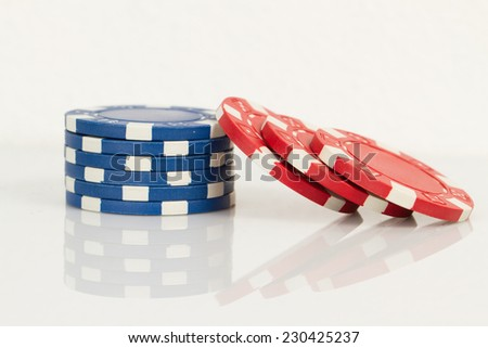 Blue and Red Playing Poker Chips in Reflective White Background - stock photo