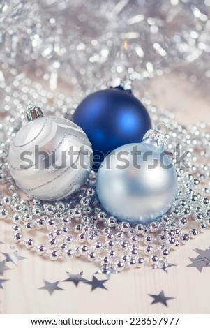 Blue and silver Christmas balls on a white wooden background - stock photo