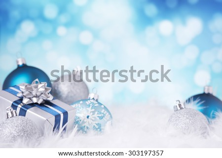 Blue and silver Christmas baubles and a gift on a soft feathery surface in front of defocused blue and white lights. - stock photo