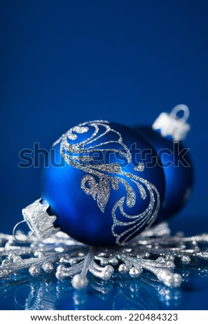 Blue and silver christmas ornaments on dark blue xmas background with space for text - stock photo