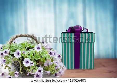 Blue and silver gift box against a wall - stock photo