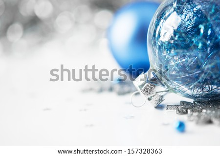 Blue and silver xmas ornaments on bright holiday background with space for text - stock photo