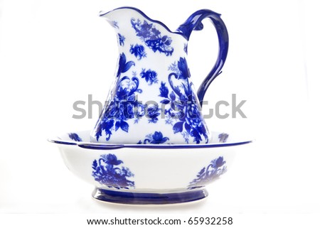 Blue and white antique pottery pitcher and basin isolated on white. - stock photo