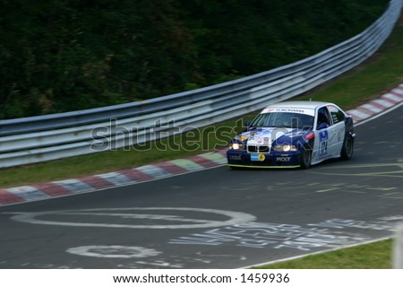 blue and white bmw sedan gt racer at night - stock photo