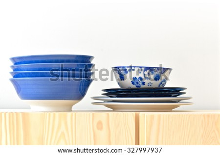 Blue and white dishes, plate and bowl on the cupboard at home  - stock photo