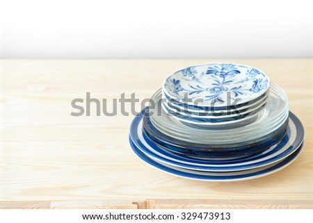 Blue and white dishes, plates and bowls on the cupboard at home - stock photo