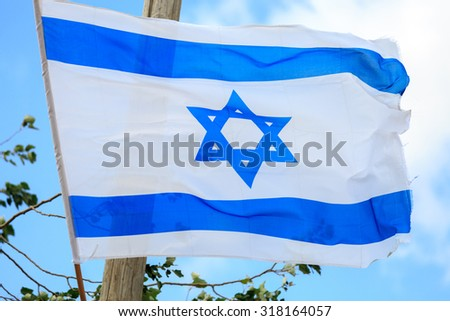 Blue and white flag of Israel waving in the wind - stock photo