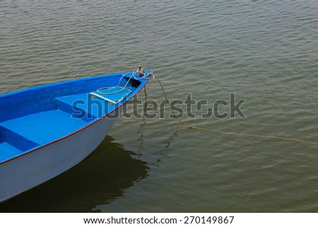 Blue and white old  boat at a the beach - stock photo