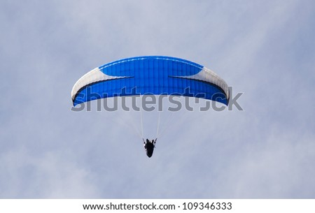 Blue and white para glider seemingly suspended against a light blue sky. - stock photo