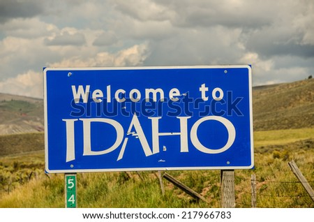 Blue and white sign welcoming travelers to the state of Idaho. - stock photo